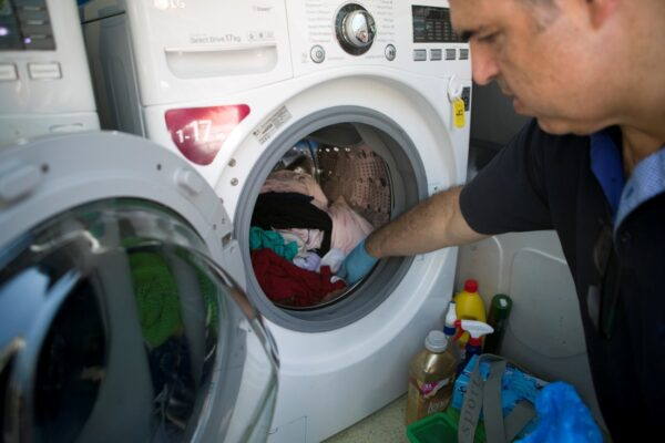 A man from Ithaca using an LG washing machine donated by LG Greece.