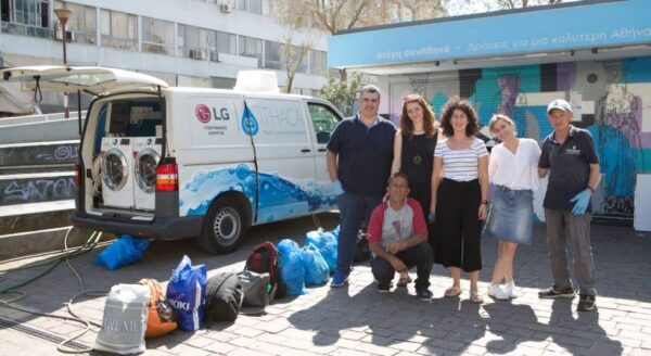 Members of Ithaca, who are making a big difference to those in need, pose next to their van that holds LG washers and dryers with the support of LG Greece.