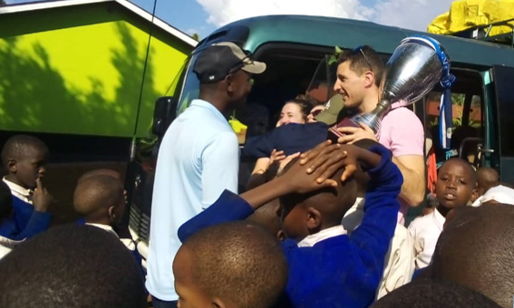 FC Cambounet being greeted at an elementary school in the village of Mbokomu, Tanzania, where they donated educational, technological and sporting equipment.