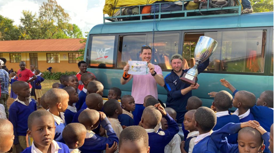 Tanzanian school children greeting two members of FC Cambounet outside their school.