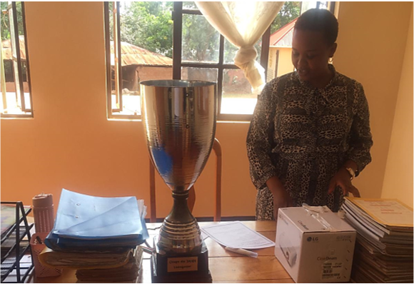 A Tanzanian teacher places the school's new LG CineBeam projector on her desk beside FC Cambounet's trophy.