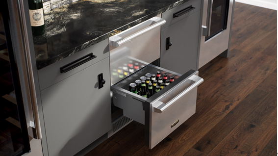A photo of this year's brand-new undercounter refrigerator which is open and filled with beverage cans and bottles.
