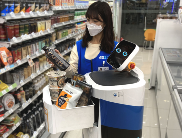 LG CLOi ServeBot working at a convenience store at LG Sciencepark as an employee fills it up with snacks for delivery.