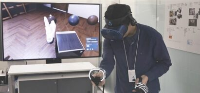 One of LG's digital designers using a VR headset and remote control to better understand a product's ability to harmonize with the environment.