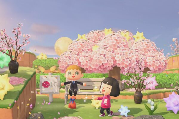 Two player avatars on popular Nintendo game 'Animal Crossing' play around a cherry blossom tree beside a wooden sign displaying the LG logo.