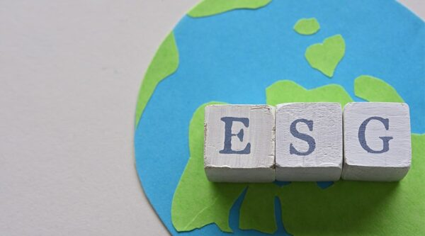 Three cubes displaying letters from the acronym ESG stand on top of a handmade picture of the world.