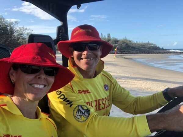 Scott Collins and a fellow member of Surf Life Saving Australia, the nation's leading non-profit organization for coastal water safety, in full uniform while operating an emergency vehicle.