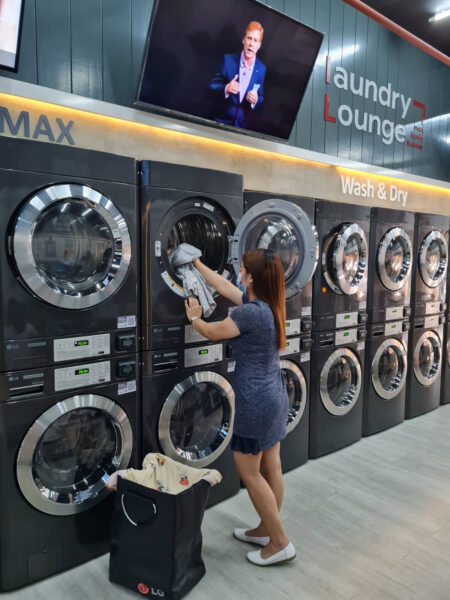 A woman is putting laundry into dryer at Laundry Lounge.