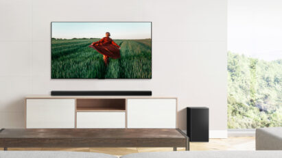 LG Soundbar sitting on a wooden cabinet below the wall-mounted LG TV to complement the TV's sound while blending effortlessly into the earthy room décor