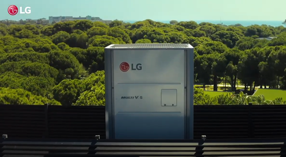 A photo of the LG Multi V Outdoor Unit installed outside a building with a sprawling forest in the background.
