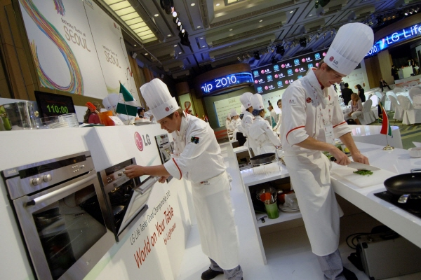 Chefs in LG's makeshift kitchen prepare culinary delights for attendees using LG's innovative cooking appliances.