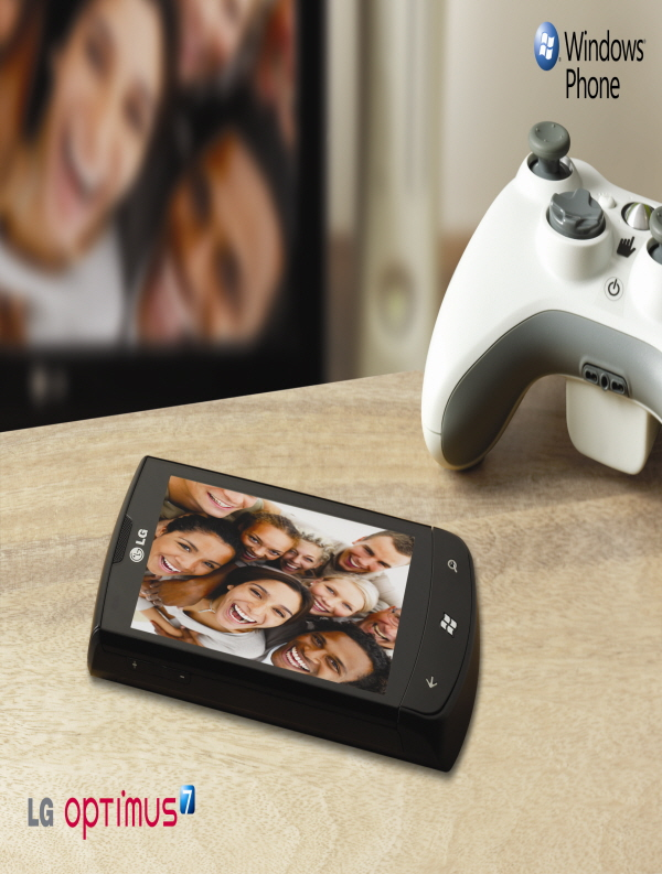 Promo shot of the LG Optimus 7 laid flat on a table next to a Microsoft Xbox 360 controller alongside the 'Windows Phone' logo