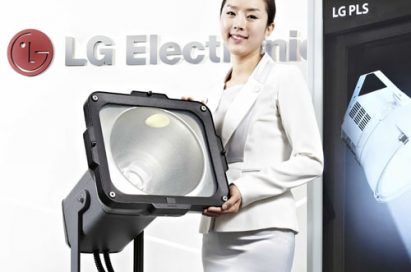 A woman poses holding LG's Plasma Lighting System (PLS) product in front of LG Electronics' logo