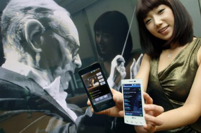A female model holds black and white LG Optimus 2Xs in front of a photo of movie soundtrack maestro, Ennio Morricone