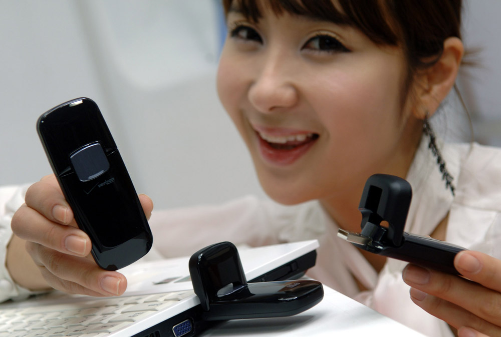 A model posing with two of LG's Verizon Wireless LTE USB Modems while one is already connected to a laptop