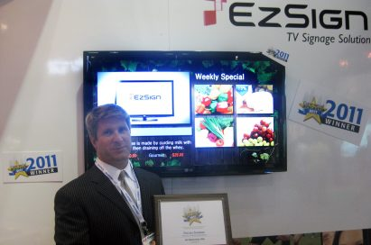 A gentleman holds up a plaque for the BEST Award in front of the LG EZSIGN TV installation at InfoComm 2011