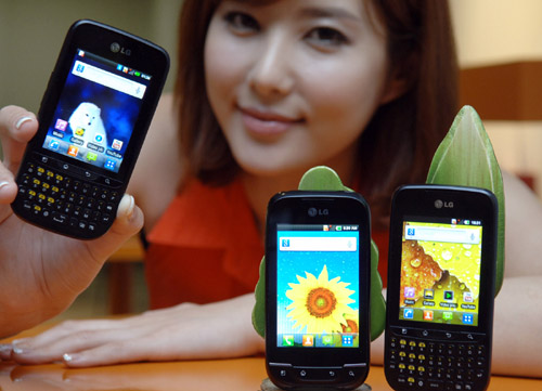 A model holds up LG Optimus Pro and shows its front view while LG Optimus Pro and LG Optimus Net are displayed in front of her