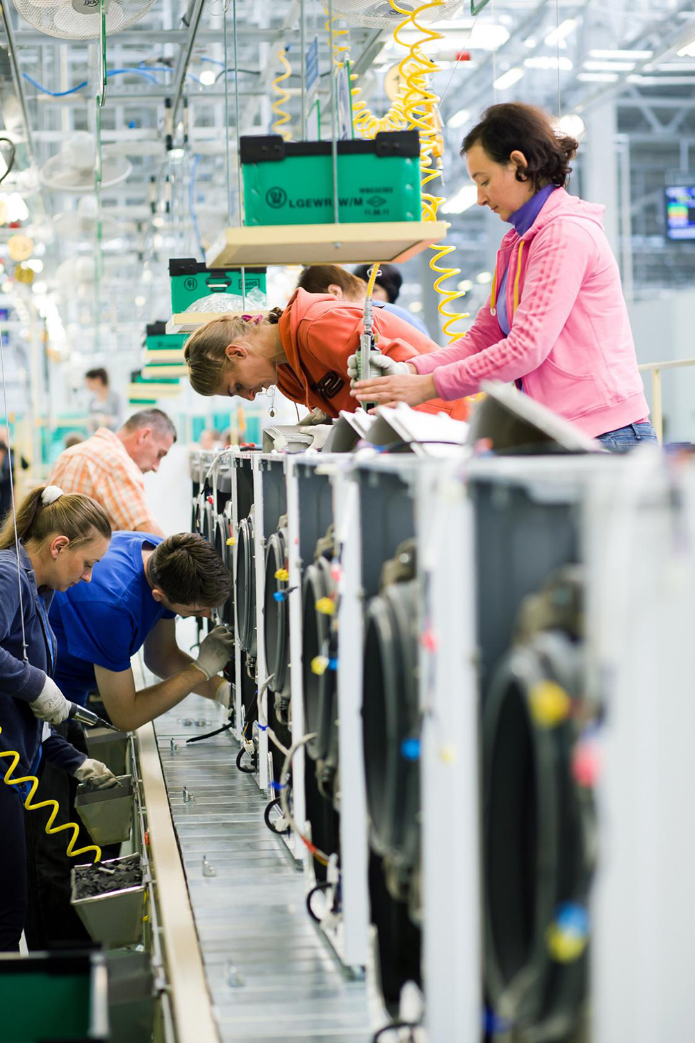 Many factory staff members assemble washing machines at an appliance manufacturing plant in Poland