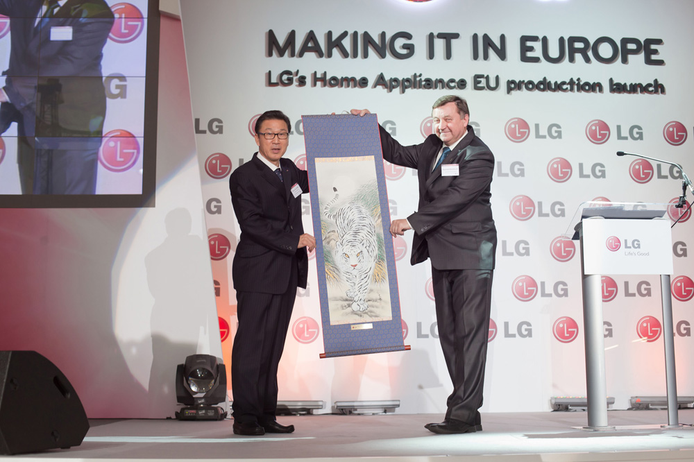 Two executives holding up a traditional Korean painting which shows white tiger at the launch event of LG's HA production facility in Poland.