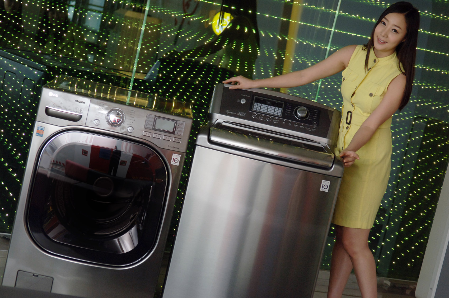 A woman posing with LG's top-load and front-load washing machines