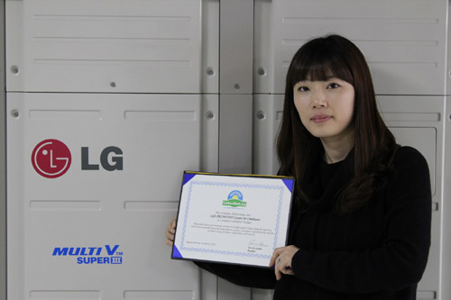 A close shot of a woman holding up LG MULTI V III's carbon-free certification letter in front of the air conditioner appliance.