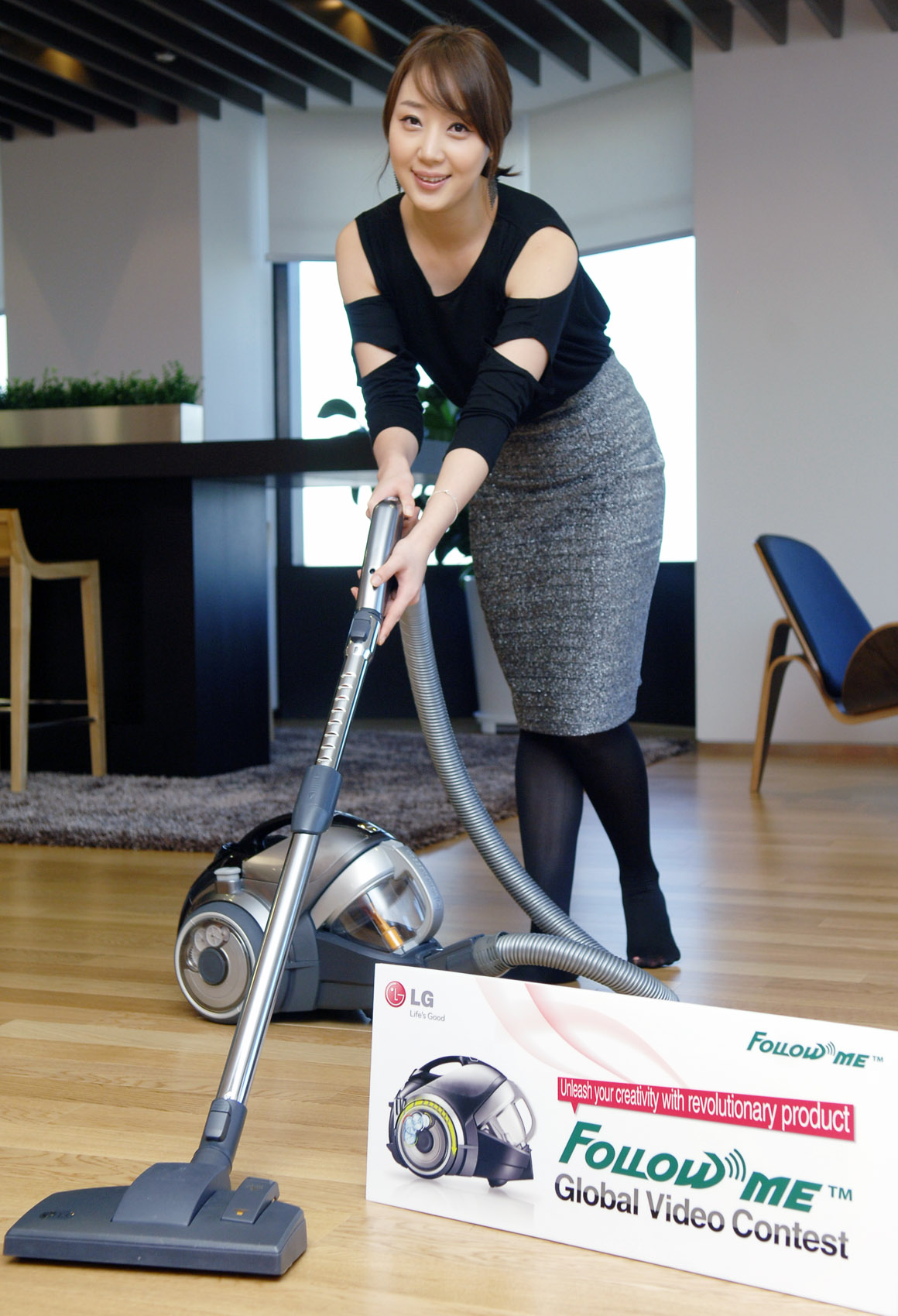A woman posing and pushing the vacuum cleaner with the banner of 'Follow Me Global Video Contest.'