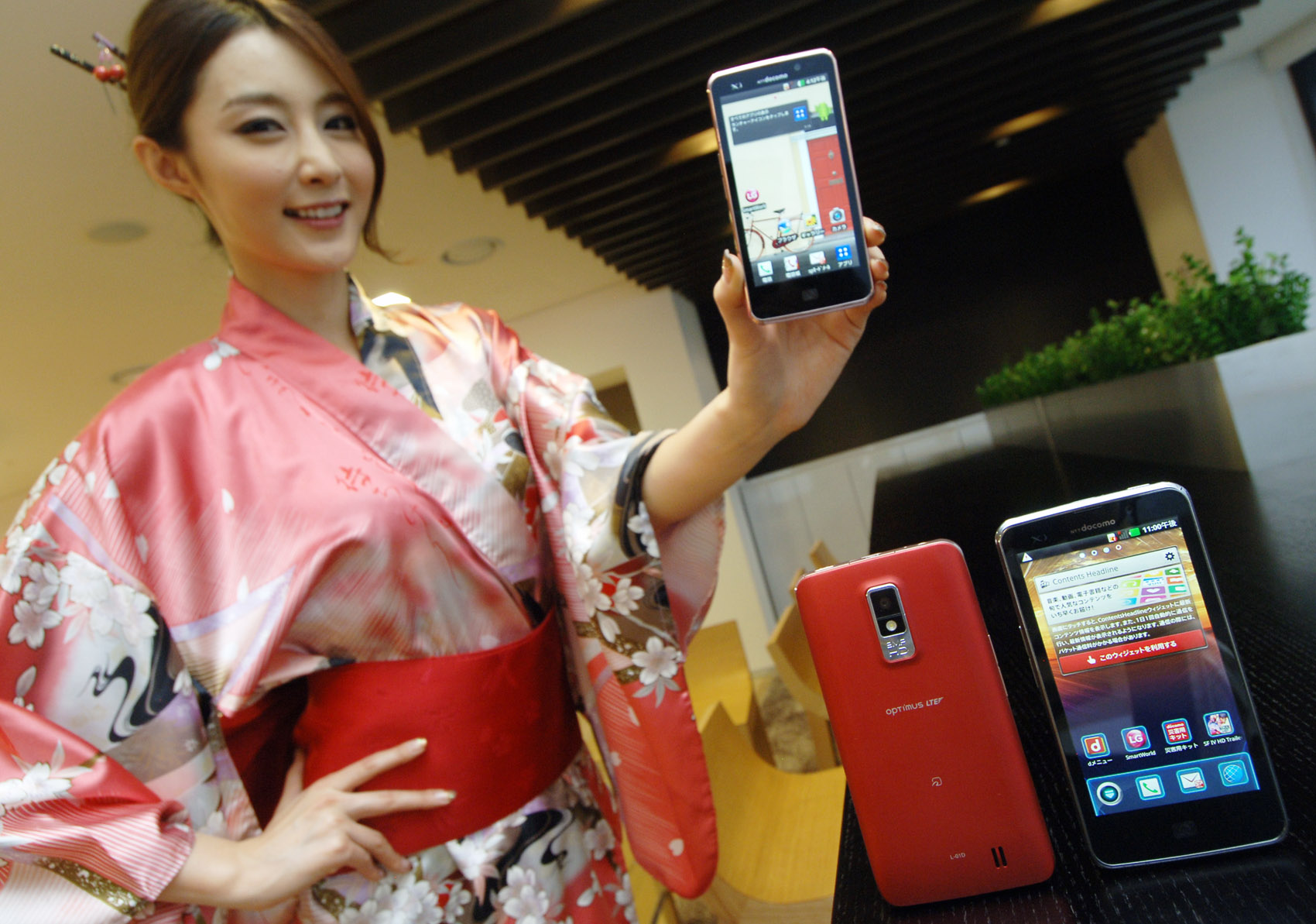 A woman in traditional Japanese clothing holds up LG Optimus LTE and shows its front view, while two LG Optimus LTEs showing front and rear views are displayed in front of her