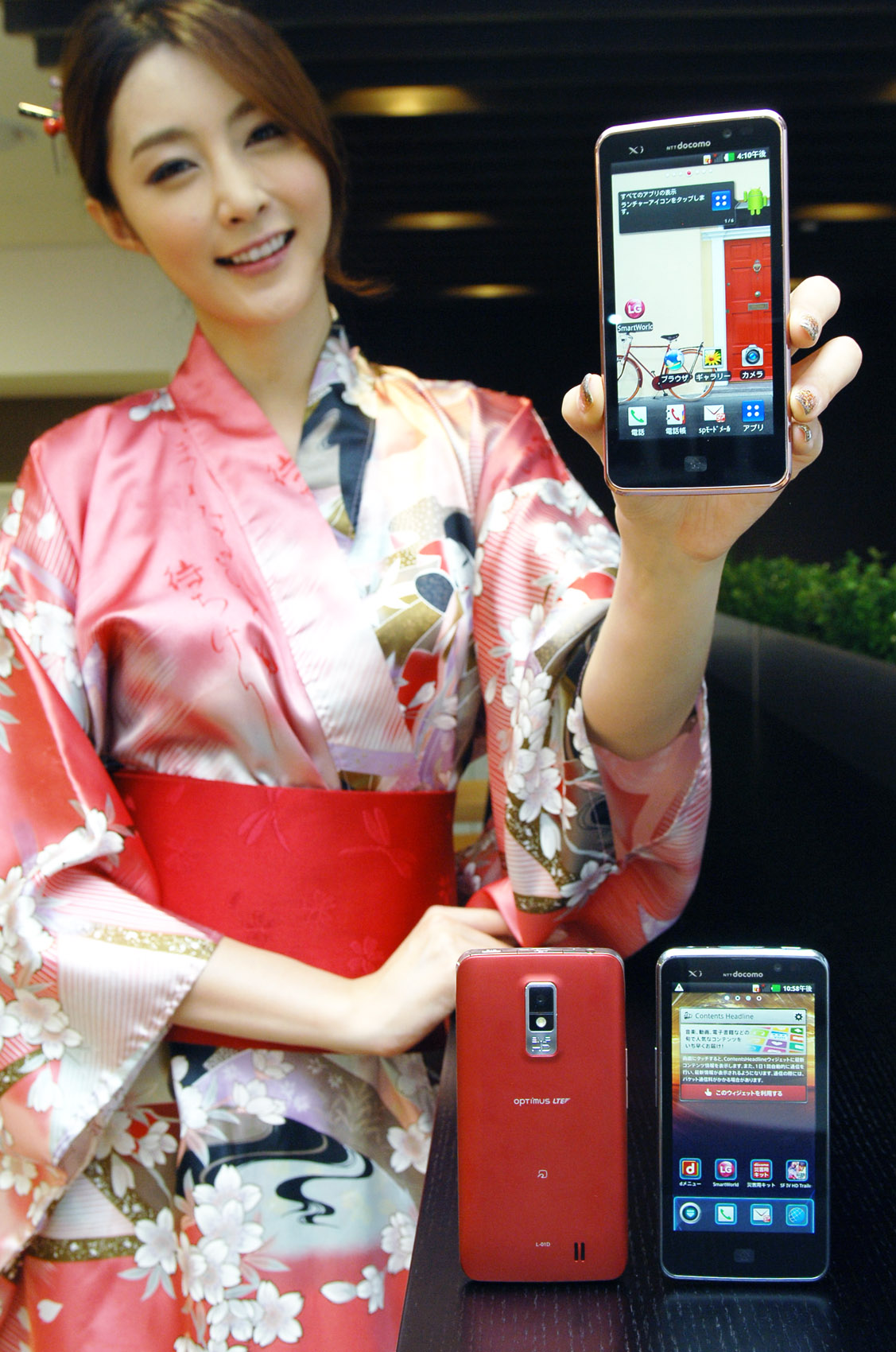 A woman in traditional Japanese clothing holds up LG Optimus LTE and shows its front view, while two LG Optimus LTEs displaying its front and back are displayed in front of her