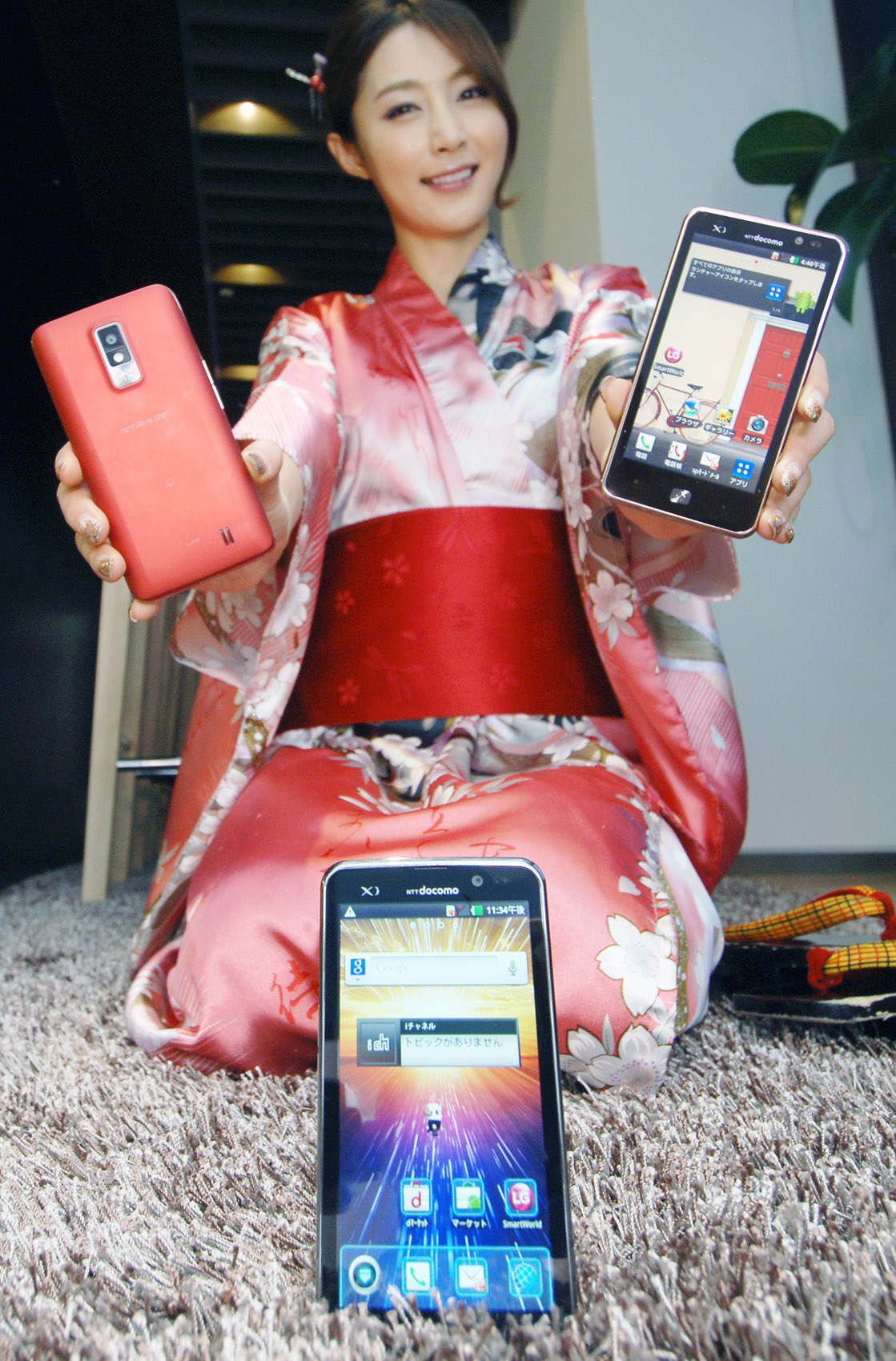 A woman in traditional Japanese clothing holds up two LG Optimus LTEs, showing the front and back, while a front view of LG Optimus LTE is displayed in front of her