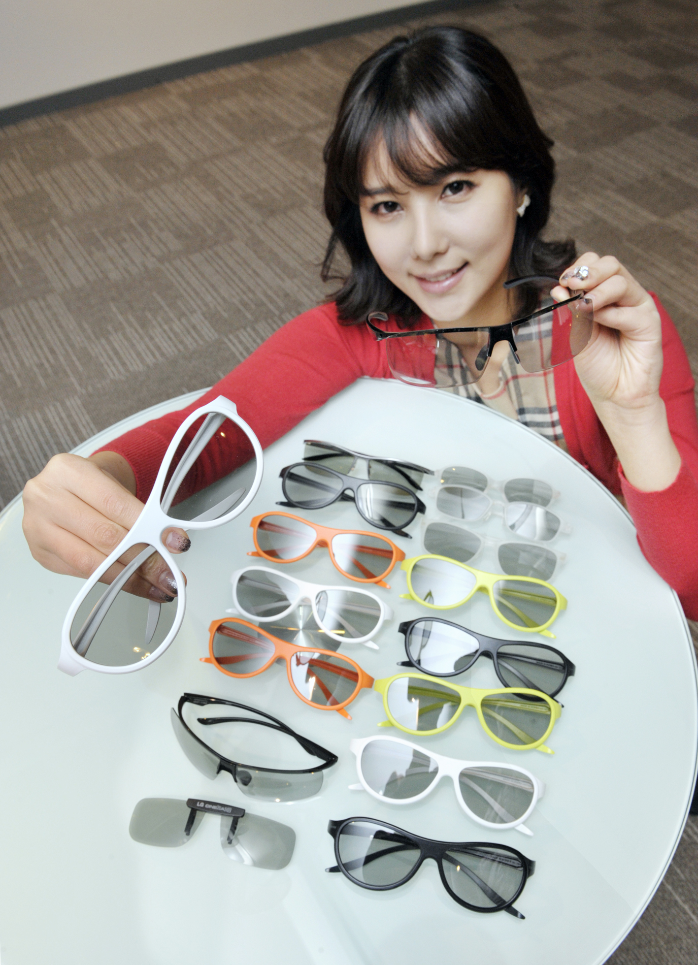 A model presenting the various types and colors of LG's new 3D glasses lineup on a table
