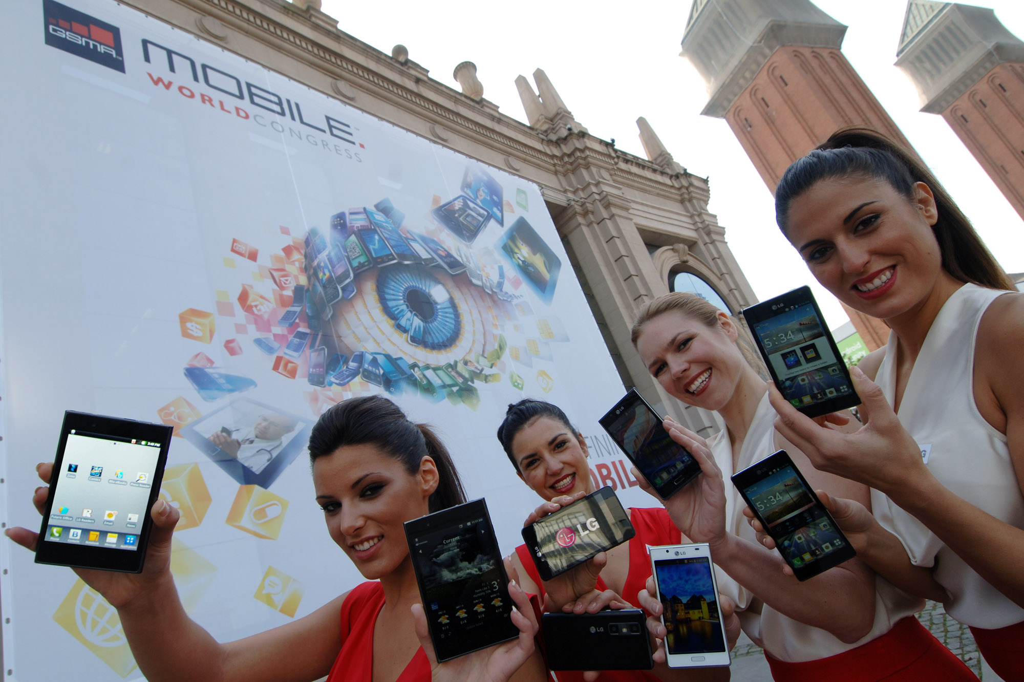 4 female models hold LG Optimus Vu:, LG Optimus 4X HD, LG Optimus 3D Max and LG Optimus L7 and show its front and rear views in front of the main entrance of Fira de Barcelona, Montjuïc venue