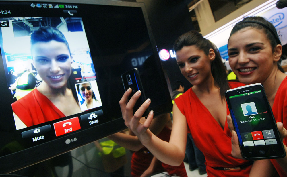 Another view of two models trying out the Voice to Video Convention feature on their LG mobile phones