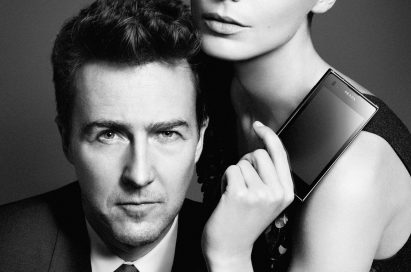Daria Werbowy poses with Edward Norton while holding up the PRADA phone by LG 3.0 with its front showing