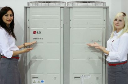 Two female models pose next to LG's MULTI V III HEAT PUMP at MCE 2012.