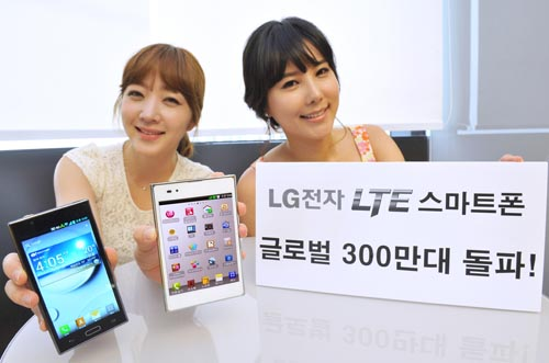 A model holds the black LG Optimus LTE in one hand and the white version in the other, while another model holds a paper panel celebrating three million sales