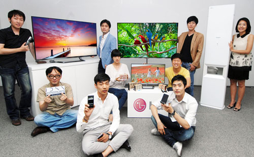 People hold an array of LG's latest products that have received accolades from the Industrial Designers Society of America (IDSA) and the International Design Excellence Awards (IDEA)
