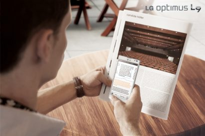 A man is using LG Optimus L9's QTranslator feature to help him read a magazine