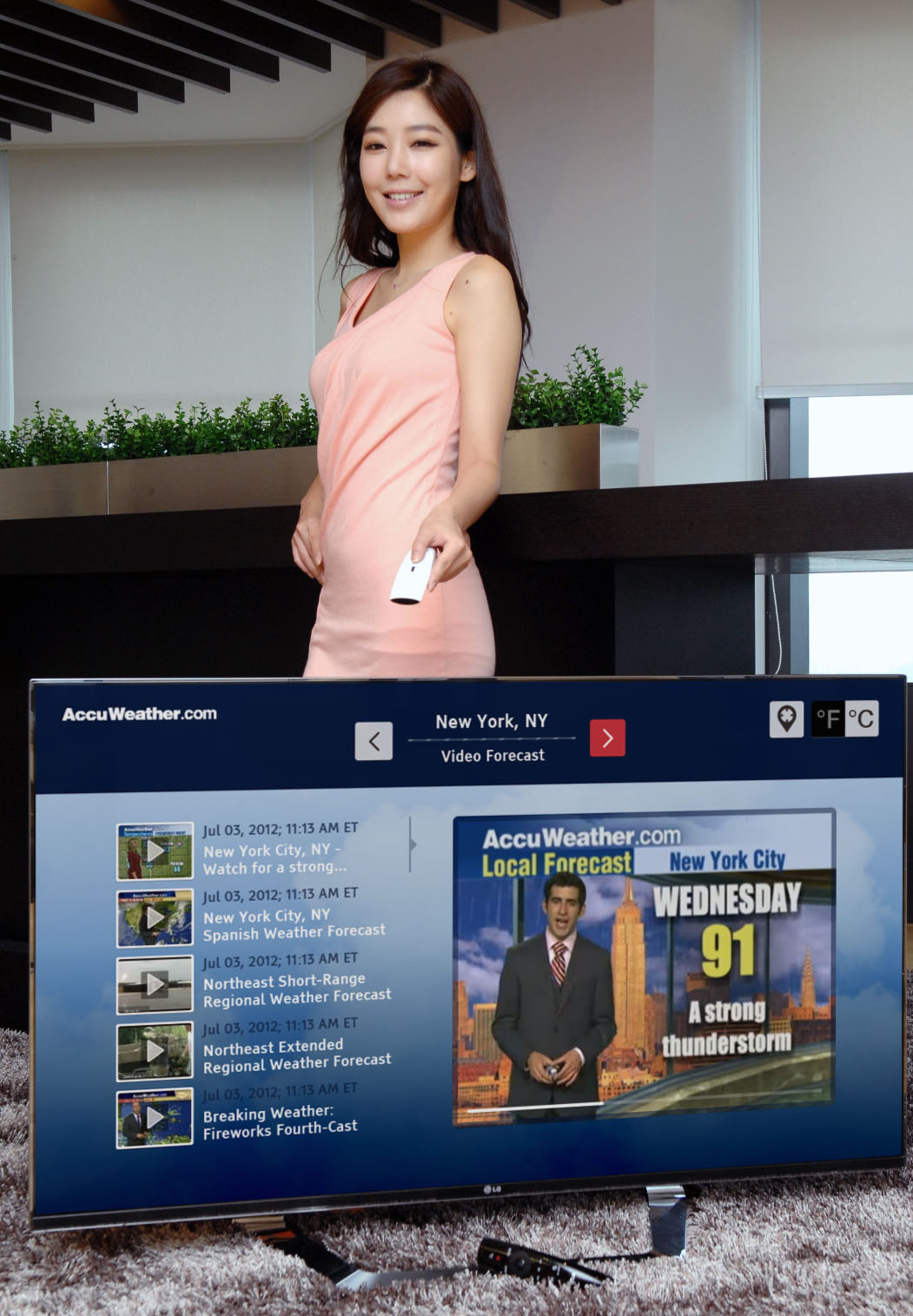 A model controlling an LG Smart TV as it displays a weather forecast channel