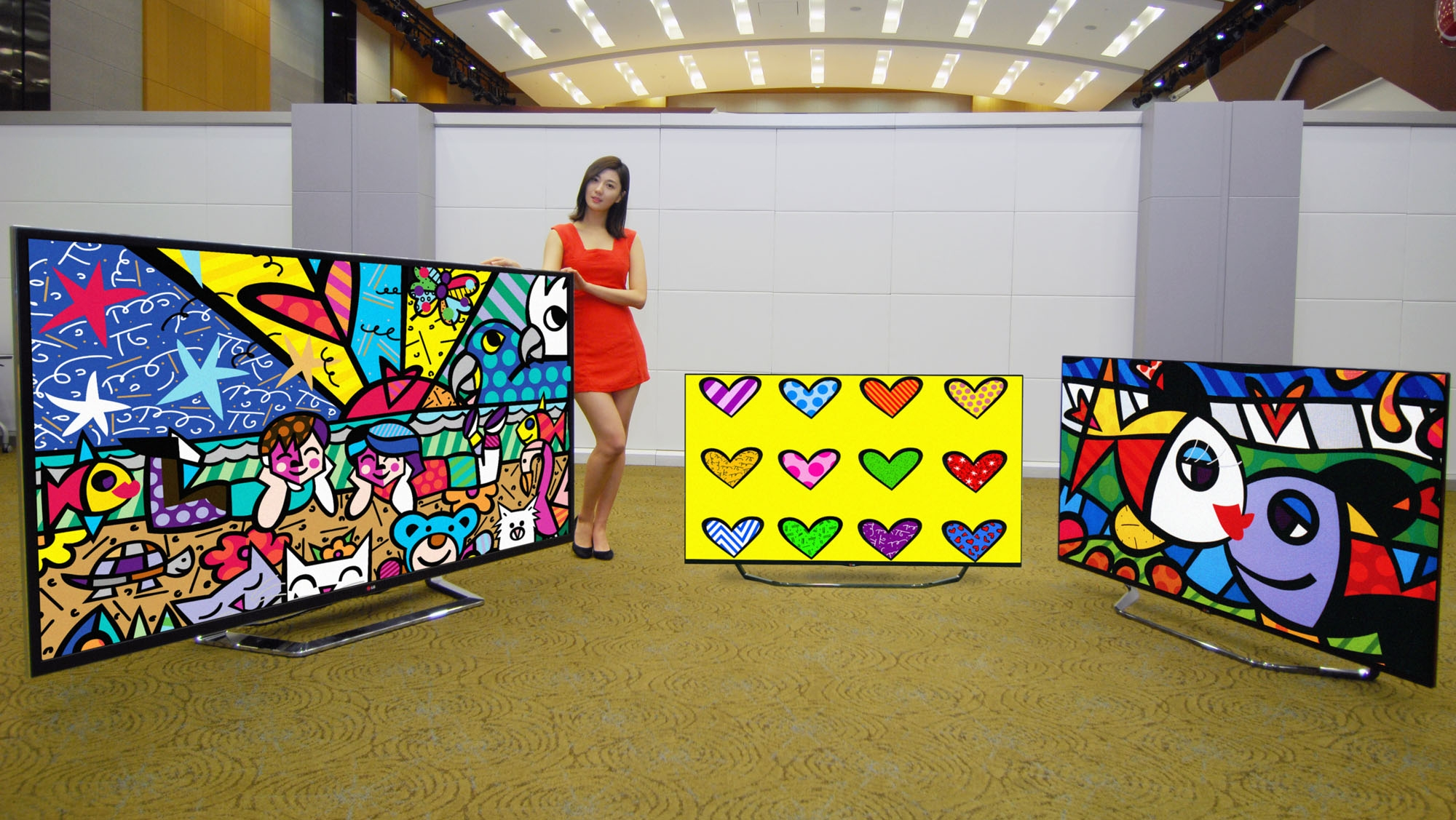 A model is presenting LG UHD TVs (84-inch, 55- and 65-inch screen models)