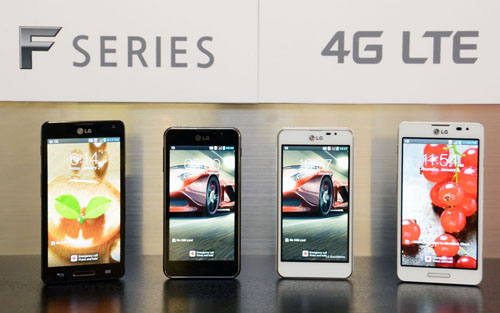 """Four of new LG Optimus F series smartphones are displayed. From left to right; Optimus F7 in black color, Optimus F5 in black color, Optimus F5 in white color, Optimus F7 in white color. A panel saying """"F SERIES 4G LTE"""" is also attached to the wall behind the handsets."""