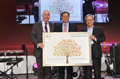 Seong-jin Jo, president and CEO of the LG Home Appliance Company, holds up the LG InnoFest 2013 slogan with two men at InnoFest 2013 in Berlin