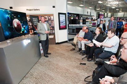 An LG representative demonstrates LG's CURVED OLED TV model 55EA9800 to attendees