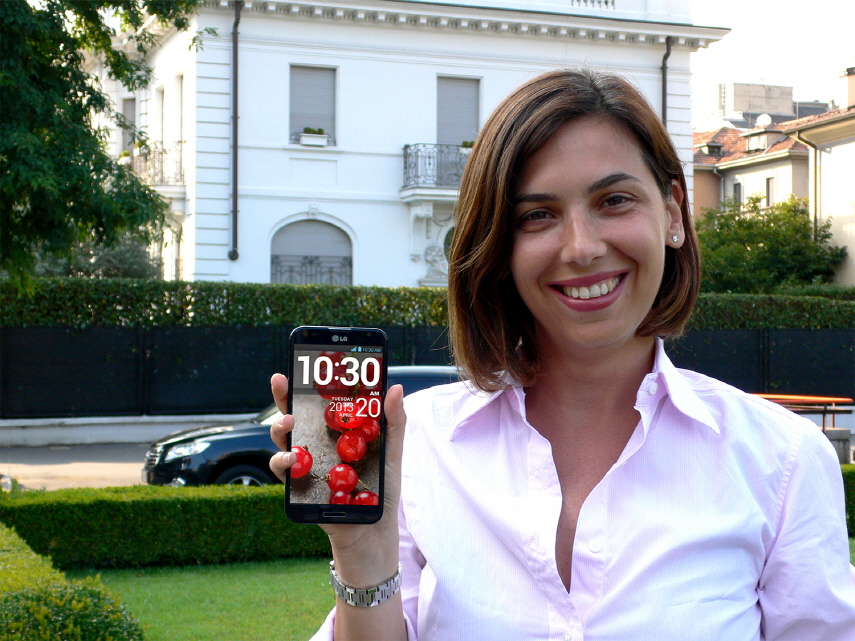 A woman posing in a garden holding the LG Optimus G Pro.