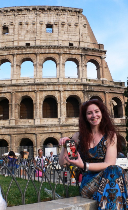 A woman posing in front of the Colosseum, Italy, while holding the LG Optimus G Pro.