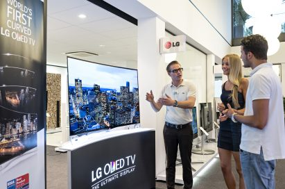 A member of staff explaining the LG CURVED OLED TV model 55EA9800 to visitors