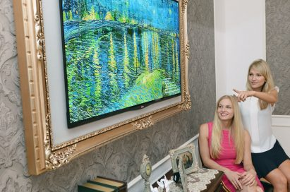 Two visitors view the LG GALLERY OLED TV in a grand golden frame at IFA 2013