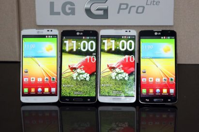 """Front views of four LG G Pro Lites displayed upright on a table, with an """" LG G Pro Lite"""" logo attached to the wall behind."""