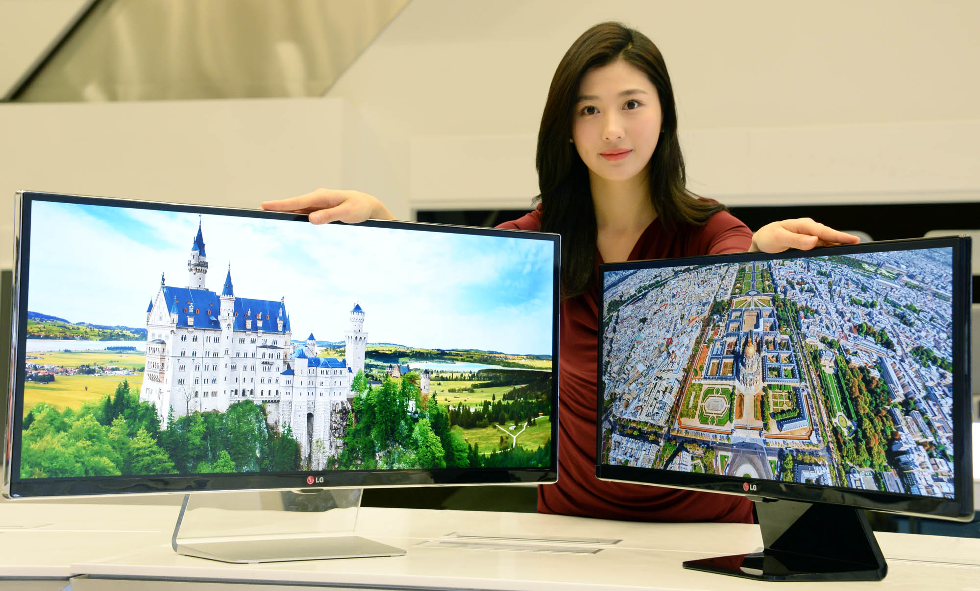 A model presenting 34-inch and 29-inch IPS 21:9 UltraWide monitors while putting her hands on both