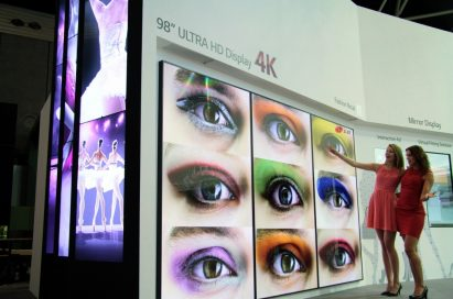 Two models demonstrating LG's 98-inch ULTRA HD display at ISE2014