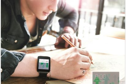 A man writes on paper while wearing the LG G Watch in Titan Black, with a small screenshot close-up of the watch's display showing Google's stock activity overlapping.